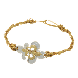 Worn gold tone wire wrapped latch bracelet featuring a two tone fleur de lis focal.