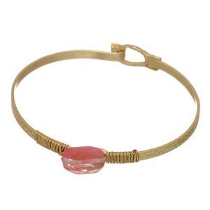 Worn gold tone latch bangle bracelet featuring a rose pink wire wrapped faceted stone.
