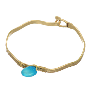 Worn gold tone wavy latch bangle bracelet with a wire wrapped blue stone.