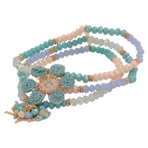 Stretch bracelet featuring turquoise, blue, and cream beads with a metal flower focal and tassel accent.
