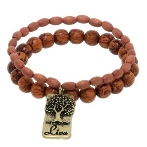 "Brown wood beaded stretch bracelet featuring a burnished gold tone plate with a tree stamped ""Live""."