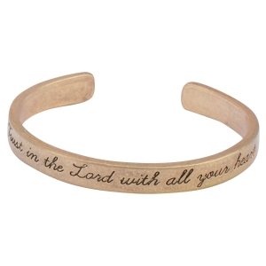 """Worn gold tone cuff bracelet stamped """"Trust in the Lord with all your heart""""."""