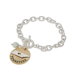 "Matte two tone toggle state bracelet with a ""TENNESSEE"" charm and a faux pearl accent. Approximately 8"" in length."