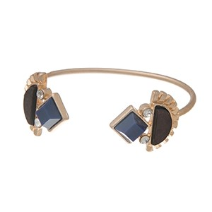 Worn gold tone cuff bracelet with a brown wood and blue diamond shaped cabochon at the opening.