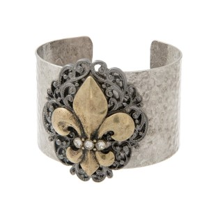 Burnished silver tone cuff bracelet with a burnished gold tone fleur de lis symbol.