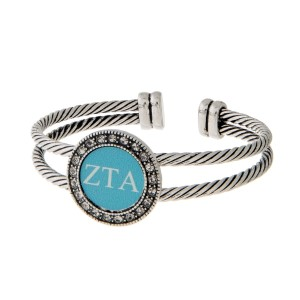 Burnished silver tone officially licensed Zeta Tau Alpha cuff bracelet with rhinestone accents.