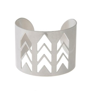 Worn silver tone cuff bracelet with a cutout chevron pattern.