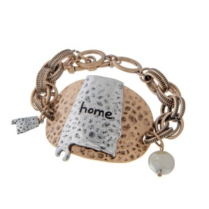 "Burnished gold tone toggle bracelet displaying a hammered plate with a burnished silver tone state of Alabama stamped ""home"". Approximately 8"" in length."