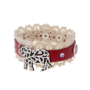 "Red faux leather cuff bracelet displaying ivory lace with a silver tone elephant and two houndstooth charms. Approximately 8 1/4"" in length."