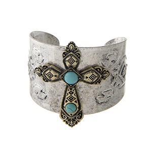 Burnished silver tone tribal inspired cuff bracelet displaying a burnished gold tone cross with turquoise stones.