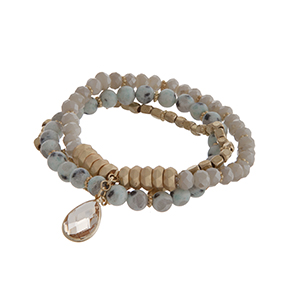 Multiple row stretch bracelet displaying amazonite, ivory, and gold tone beads with a topaz teardrop shape cabochon.