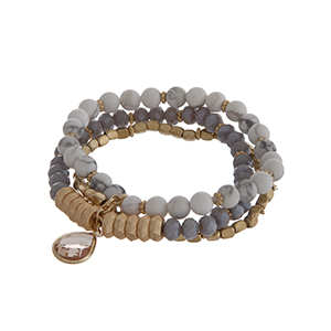 Multiple row stretch bracelet displaying white, gray, and gold tone beads with a light topaz teardrop shape cabochon.
