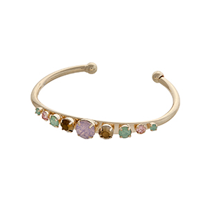 Gold tone cuff bracelet displaying a row of pink, brown, and mint cabochons.