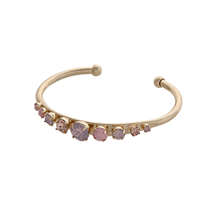 Gold tone cuff bracelet displaying a row of pink cabochons.
