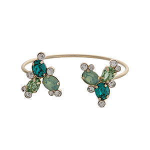Gold tone cuff bracelet displaying mint and green rhinestones at the opening.
