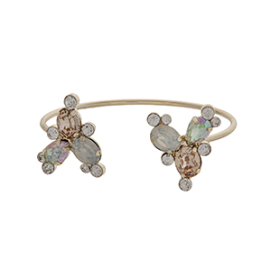Gold tone cuff bracelet displaying white opal and champagne rhinestones at the opening.