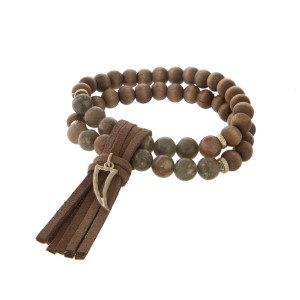 Two strand green stone and brown wood bead stretch bracelet with a brown fabric tassel and gold tone horn charm.