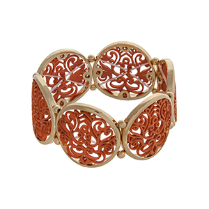 Gold tone stretch bracelet displaying coral filigree design disk.