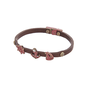 Brown faux leather magnetic bracelet featuring a sailboat, anchor, and captain's wheel charms with a coral patina finish.