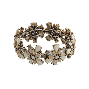 Burnished gold tone stretch bracelet with ivory and clear flower cabochons.