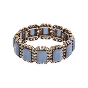Burnished gold tone stretch bracelet displaying blue cabochons surrounded by white opal rhinestones.