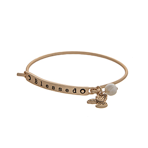 "Matte gold tone latch bangle bracelet displaying a bar stamped ""Blessed"" with an angle charm and a faux ivory pearl."