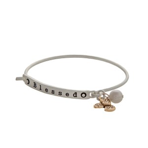 "Matte silver tone latch bangle bracelet displaying a bar stamped ""Blessed"" with an angel charm and a faux ivory pearl."