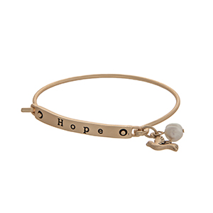 "Matte gold tone latch bangle bracelet displaying a bar stamped ""HOPE"" with a dove charm and a faux ivory pearl."