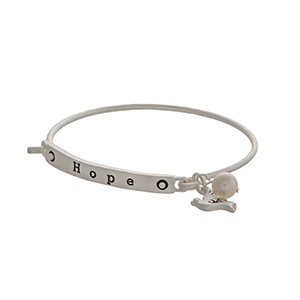 "Matte silver tone latch bangle bracelet displaying a bar stamped ""HOPE"" with a dove charm and a faux ivory pearl."