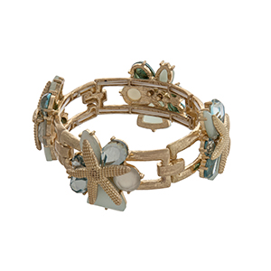 Gold tone stretch bracelet displaying aqua cabochons with layered starfish.