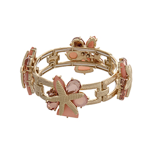 Gold tone stretch bracelet displaying pink cabochons with layered starfish.