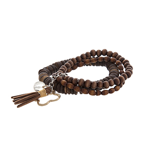 Three strand wood bead and gold tone quatrefoil stretch bracelet with a light brown tassel.