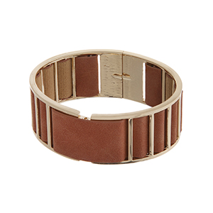 Gold tone cuff bracelet displaying brown fabric with a back spring lever.
