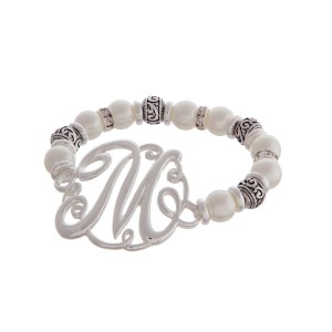 """Silver tone and pearl beaded stretch bracelet featuring the letter """"M"""" initial and accented with clear rhinestones."""
