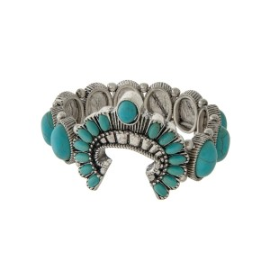 Silver tone stretch bracelet with turquoise stones and a squash blossom focal.
