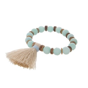 Mint green beaded stretch bracelet with wooden accents and an ivory tassel.