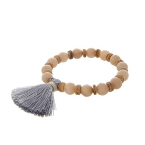Beige beaded stretch bracelet with wooden accents and a gray tassel.