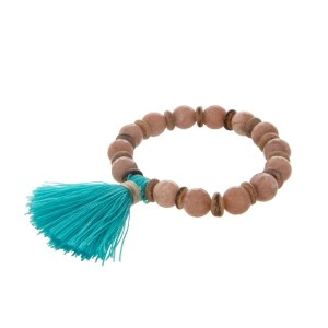 Beige beaded stretch bracelet with wooden accents and a turquoise tassel.