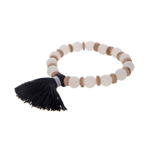 White beaded stretch bracelet with wooden accents and a black tassel.