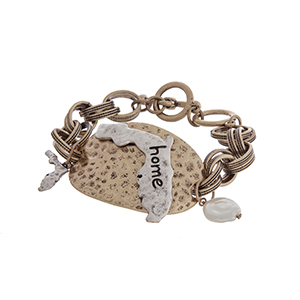"""Burnished gold tone toggle bracelet displaying a hammered plate with a burnished silver tone state of Florida stamped """"home"""". Approximately 8"""" in length."""