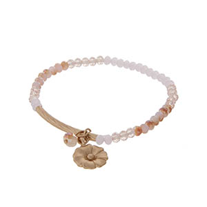 Pink beaded stretch bracelet with gold ton hardware and a flower charm.