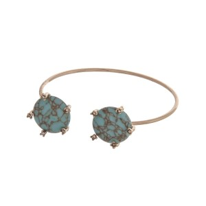Dainty gold tone cuff bracelet with turquoise stones accented with clear rhinestones.
