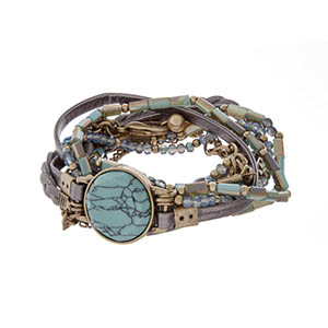 Blue wrap bracelet with gold tone hardware, gray leather, and a turquoise stone.