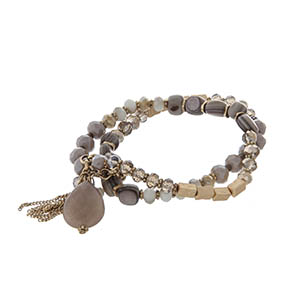 Beaded stretch bracelet set with taupe beads and gold tone hardware.