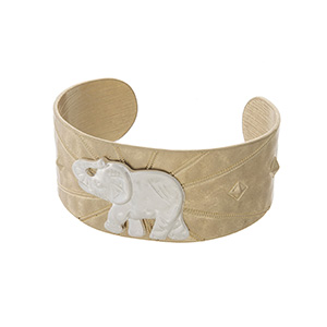 Worn gold tone cuff bracelet with a silver elephant focal.