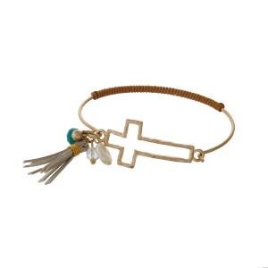 Gold tone bangle bracelet with a latch closure displaying a cross shape, brown cord, a tassel, turquoise and pearl bead charms.