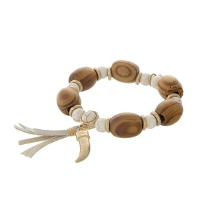 Wooden beaded stretch bracelet with ivory beads, horn and tassel charms.