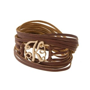 "Brown faux leather wrap bracelet with a gold tone 'K' initial focal. Approximately 22"" in length."