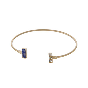 Dainty gold tone cuff bracelet with a navy blue stone accented with clear rhinestones.