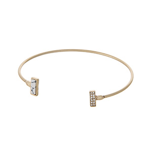 Dainty gold tone cuff bracelet with a white stone accented with clear rhinestones.